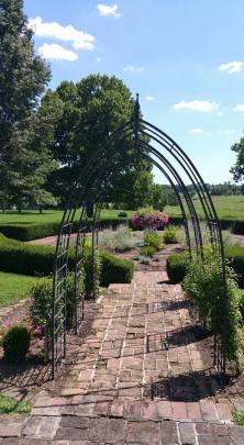 """Entrance to the side garden. """"The rose garden seen today is in the same location dating back to Green Clay's time (late 1790s)."""" The urn in the center belonged to the Clay family."""